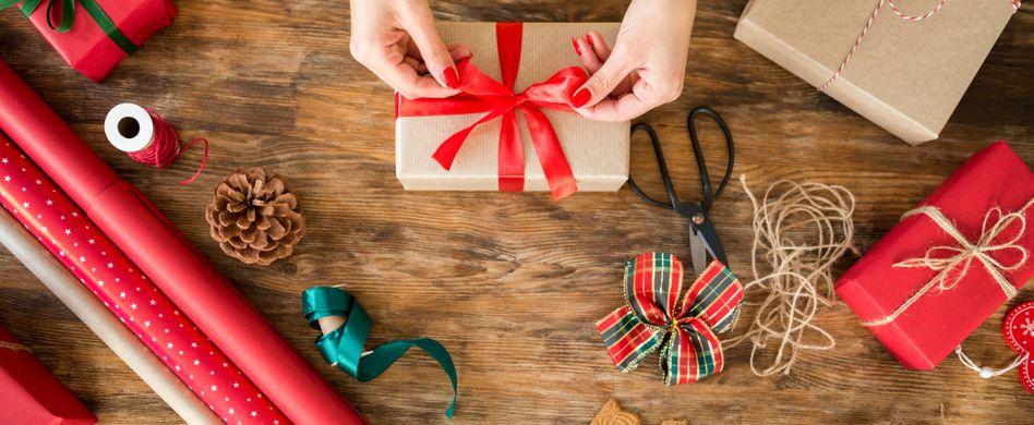 frau bindet schleife um weihnachtsgeschenk