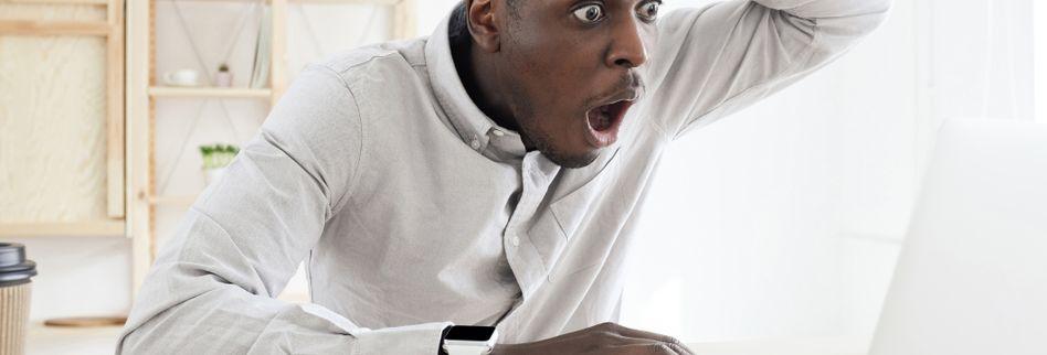 mann schaut erschrocken auf laptop