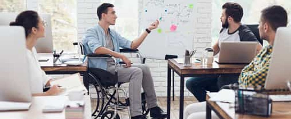 Ein Mann im Rollstuhl hält eine Präsentation in einem Büro vor mehreren Personen.