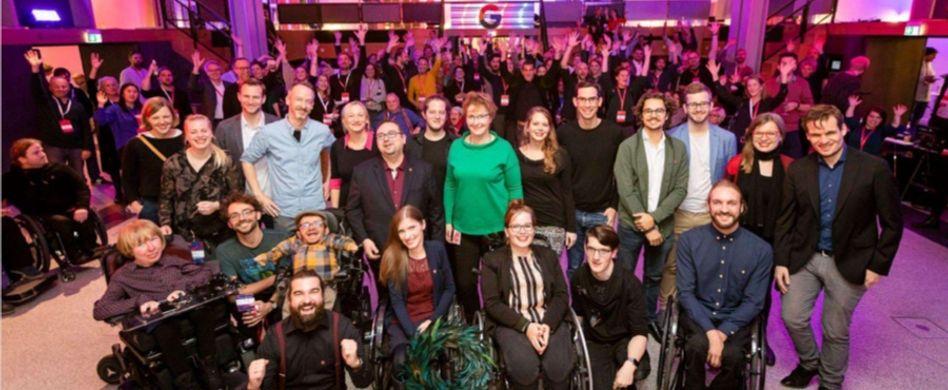 Eine große Gruppe von Menschen mit und ohne Behinderungen positioniert sich in einem Tanzsaal zu einem geselligen Gruppenbild.